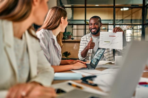 Homem de negócios afro-americano jovem bonito mostrando um gráfico no papel para um grupo de colegas sentados em uma mesa com laptops em um escritório moderno.
