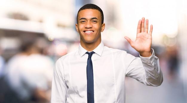 Homem de negócios afro americano novo que sauda com a mão com expressão feliz na cidade