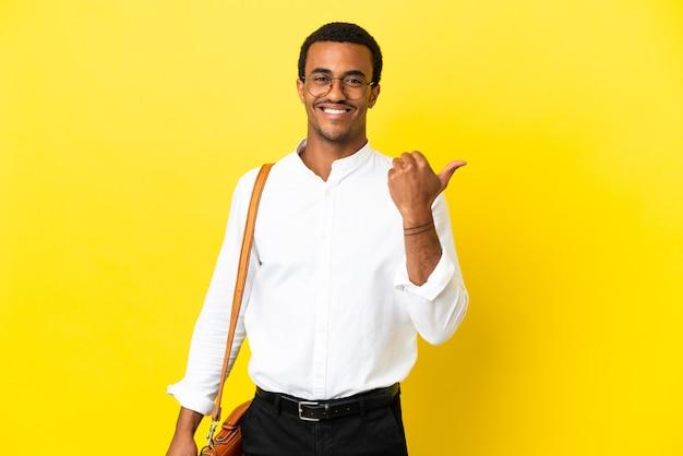 Homem de negócios afro-americano sobre fundo amarelo isolado apontando para o lado para apresentar um produto