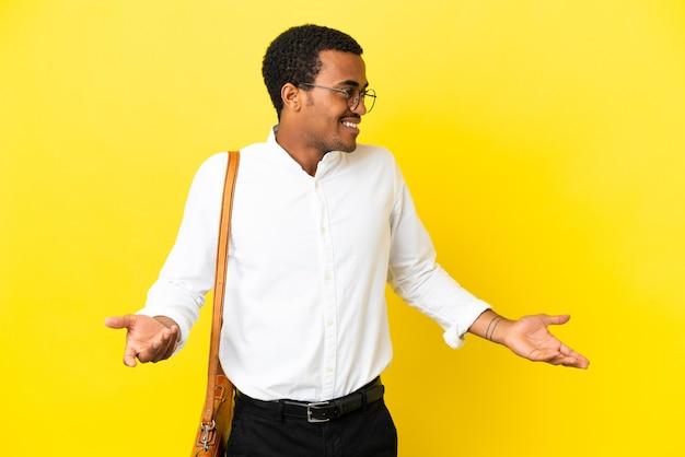 Homem de negócios afro-americano sobre fundo amarelo isolado com expressão de surpresa ao olhar para o lado