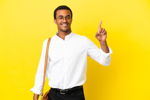 Homem de negócios afro-americano sobre fundo amarelo isolado, mostrando e levantando um dedo em sinal dos melhores