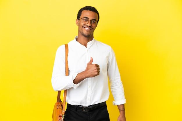 Homem de negócios afro-americano sobre fundo amarelo isolado orgulhoso e satisfeito