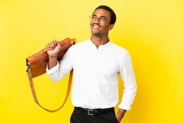 Homem de negócios afro-americano sobre fundo amarelo isolado pensando em uma ideia enquanto olha para cima