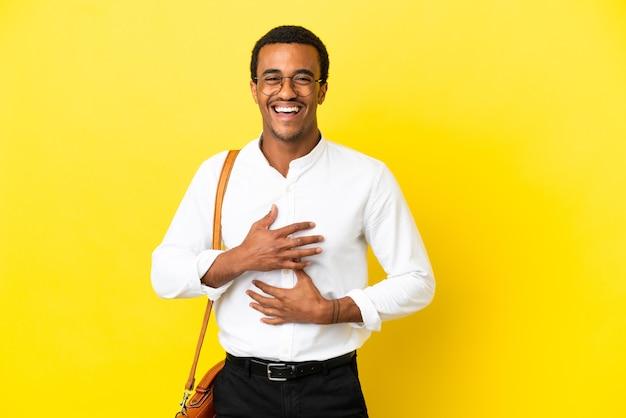 Homem de negócios afro-americano sobre fundo amarelo isolado sorrindo muito
