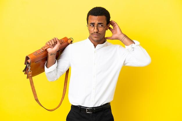 Homem de negócios afro-americano sobre fundo amarelo isolado, tendo dúvidas