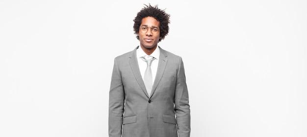 Homem de negócios afro-negro a sorrir positivamente e com confiança, parecendo satisfeito, amigável e feliz