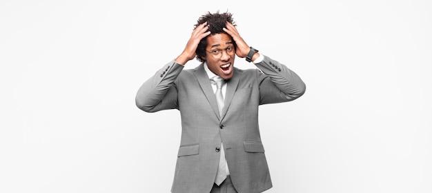 Homem de negócios afro-negro levantando as mãos para a cabeça, boquiaberto, sentindo-se extremamente sortudo, surpreso, animado e feliz