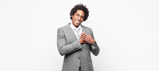 Homem de negócios afro-negro se sentindo romântico, feliz e apaixonado, sorrindo alegremente e segurando o coração de mãos dadas