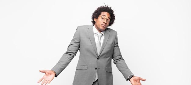 Homem de negócios afro-negro se sentindo sem noção e confuso, sem fazer ideia, absolutamente perplexo com uma aparência idiota ou tola