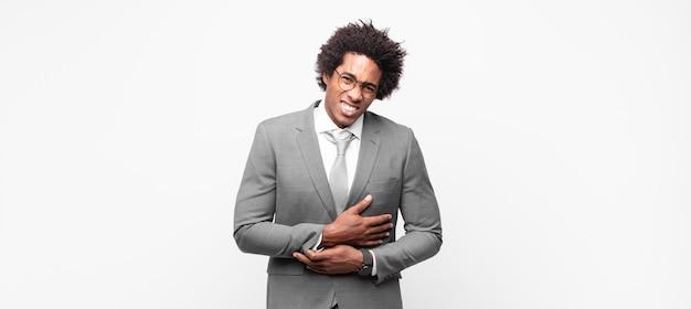 Homem de negócios afro-negro sentindo-se ansioso, doente, doente e infeliz, com uma forte dor de estômago ou gripe