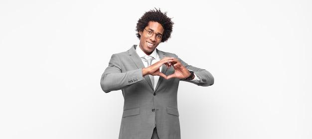 Homem de negócios afro negro sorrindo e se sentindo feliz, fofo, romântico e apaixonado, fazendo formato de coração com as duas mãos