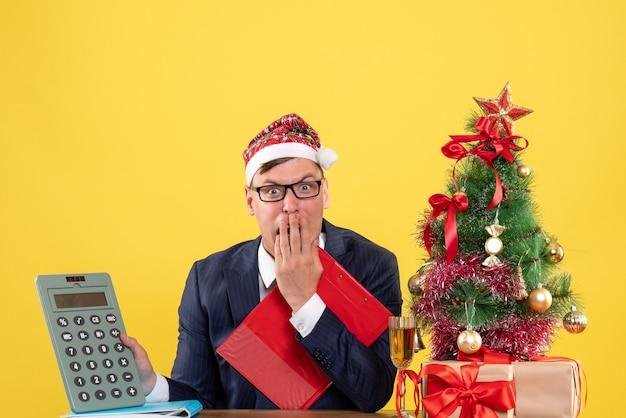 Homem de negócios agitado de vista frontal segurando uma calculadora, sentado à mesa perto da árvore de natal e presentes em fundo amarelo
