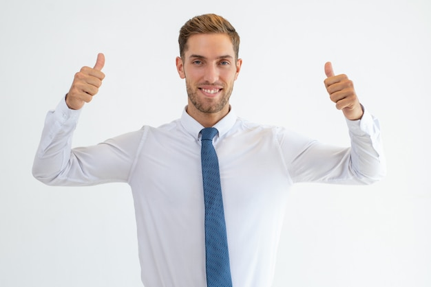 Homem de negócios alegre aparecendo polegares e olhando para a câmera