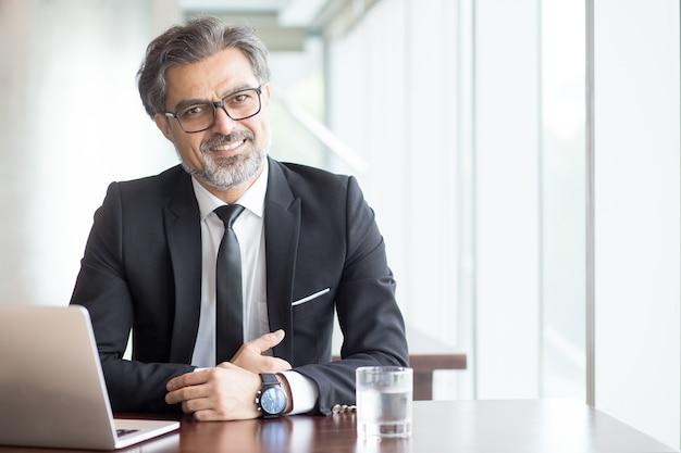 Homem de negócios alegre em óculos no escritório