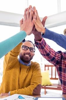 Homem de negócios alegre fazendo high five com equipe no escritório criativo