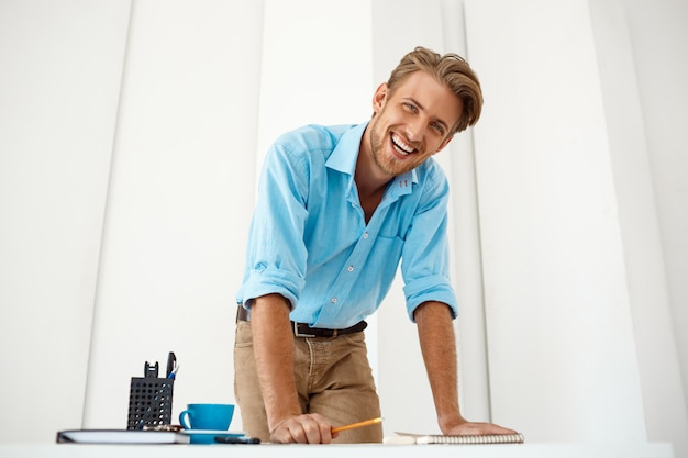 Homem de negócios alegre seguro considerável novo que está de pé na tabela sobre o bloco de notas que olha sorrindo. interior de escritório moderno branco.
