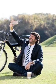 Homem de negócios alegre tomando selfie ao ar livre
