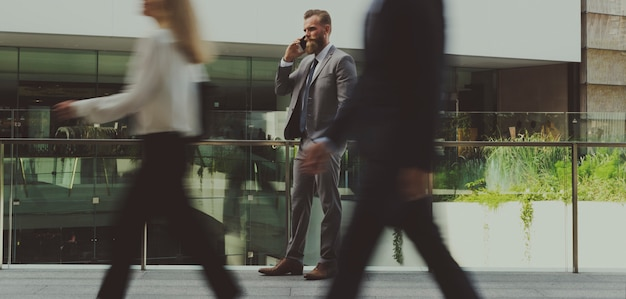 Homem de negócios alemão falando em um telefone e as pessoas passando por ele