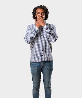 Homem de negócios americano africano bonito cobrindo a boca, símbolo do silêncio e repressão, tentando não dizer nada