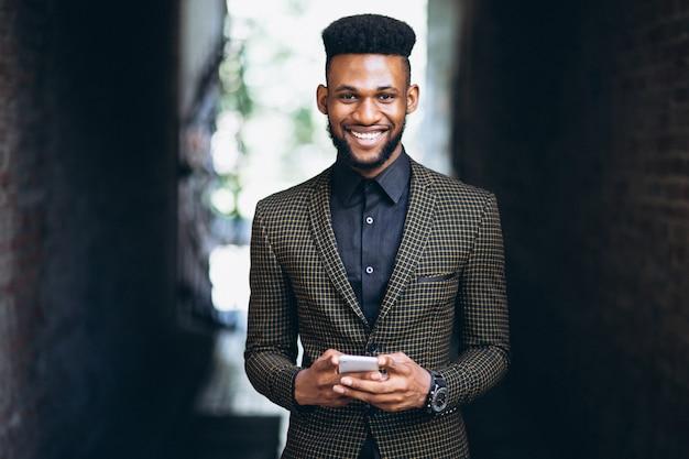 Homem de negócios americano africano com telefone