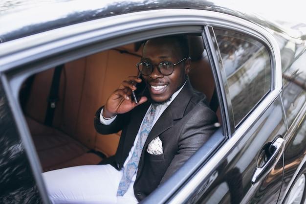 Homem de negócios americano africano no carro