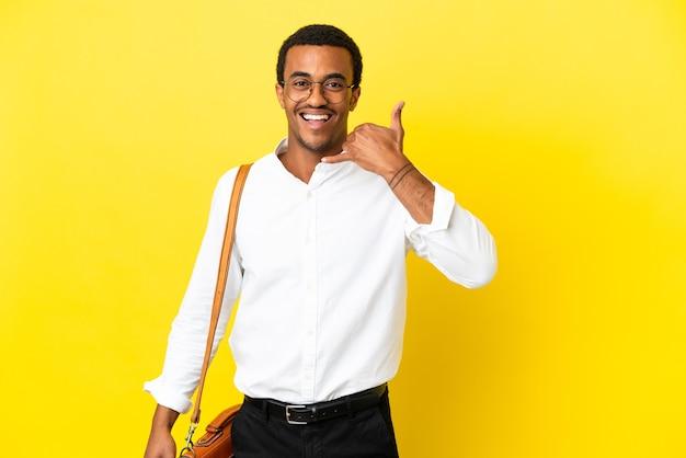 Homem de negócios americano africano sobre fundo amarelo isolado, fazendo gesto de telefone. ligue-me de volta sinal