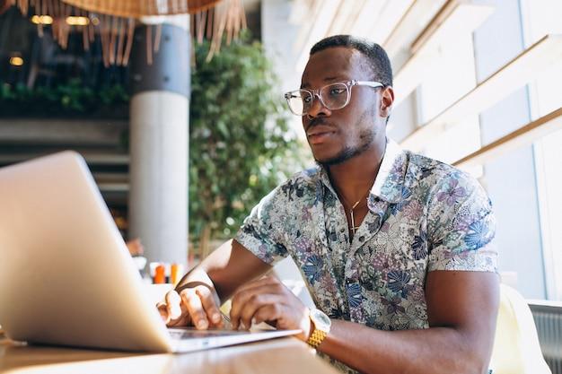 Homem de negócios americano africano trabalhando com laptop em um café