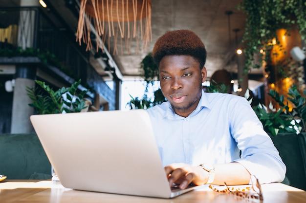 Homem de negócios americano africano trabalhando com laptop