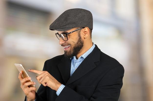 Homem de negócios americano africano usando telefone celular