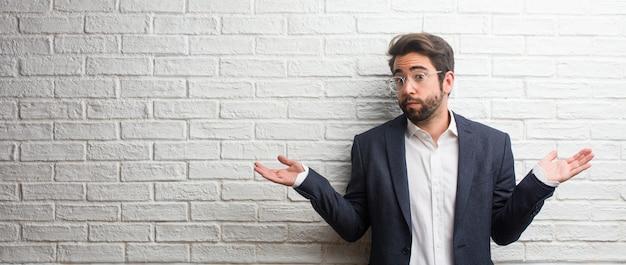 Homem de negócios amigável jovem duvidando e encolher os ombros, conceito de indecisão e insegurança, incerto sobre algo