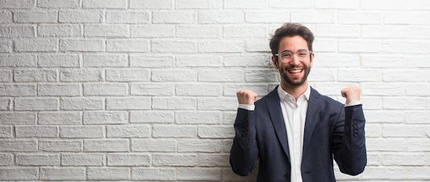 Homem de negócios amigável jovem muito feliz e animado, levantando os braços, celebrando uma vitória ou