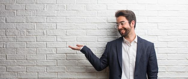 Homem de negócios amigável jovem segurando algo com as mãos, mostrando um produto