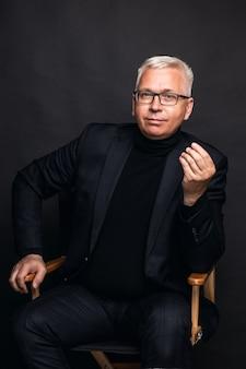 Homem de negócios amigável usando óculos e terno posando com um sorriso para a câmera em um fundo preto de estúdio com espaço de cópia