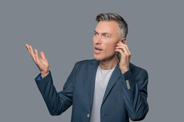Homem de negócios animado falando por smartphone