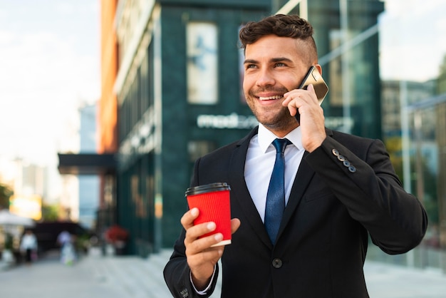 Homem de negócios ao ar livre bebendo café e falando ao telefone