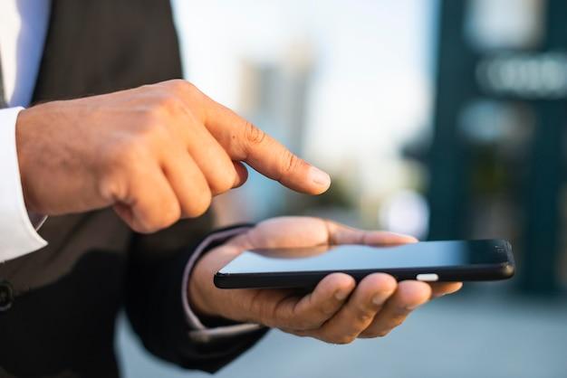 Homem de negócios ao ar livre em close-up e telefone celular