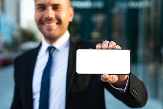 Homem de negócios ao ar livre mostrando um telefone de cópia espacial