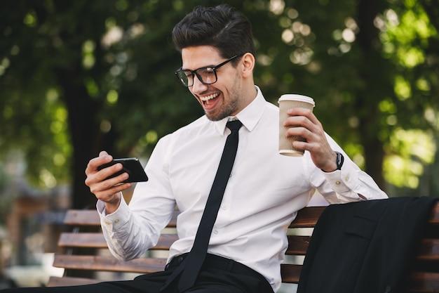 Homem de negócios ao ar livre no parque jogar jogos por telefone, bebendo café. Foto Premium