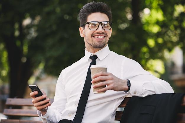 Homem de negócios ao ar livre no parque usando telefone celular, bebendo café.