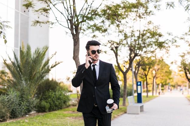 Homem de negócios ao telefone no parque