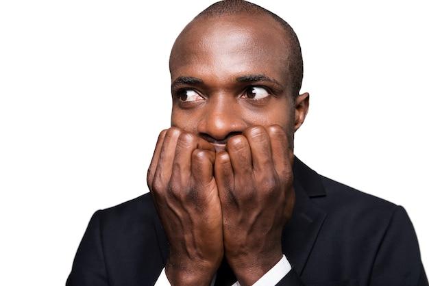 Homem de negócios apavorado. jovem africano apavorado em trajes formais, segurando os dedos na boca e olhando para longe, isolado no fundo branco