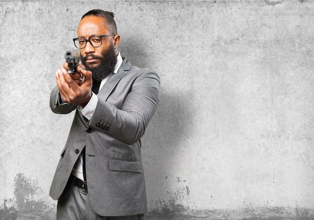 Homem de negócios apontando com uma pistola