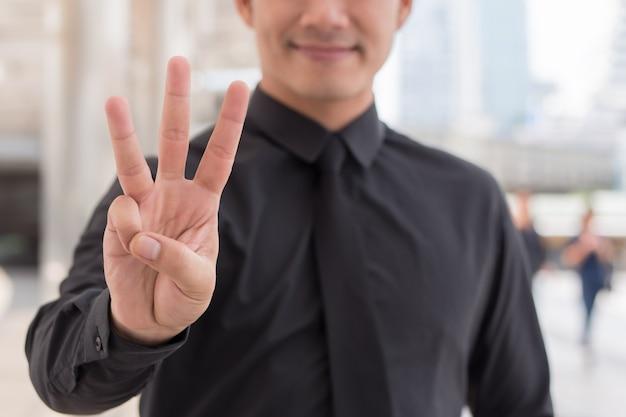 Homem de negócios apontando para cima o gesto de dedo número 3