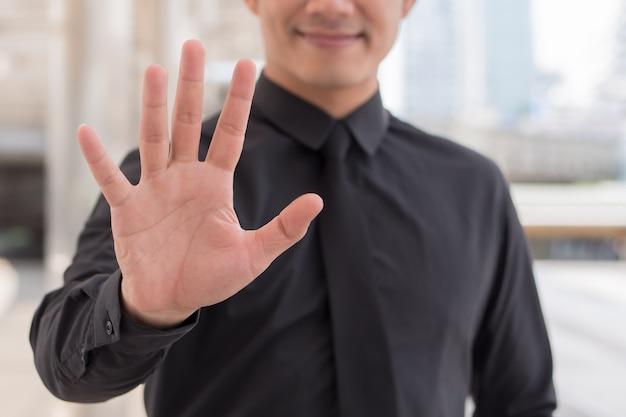 Homem de negócios apontando para o gesto com o dedo número 5