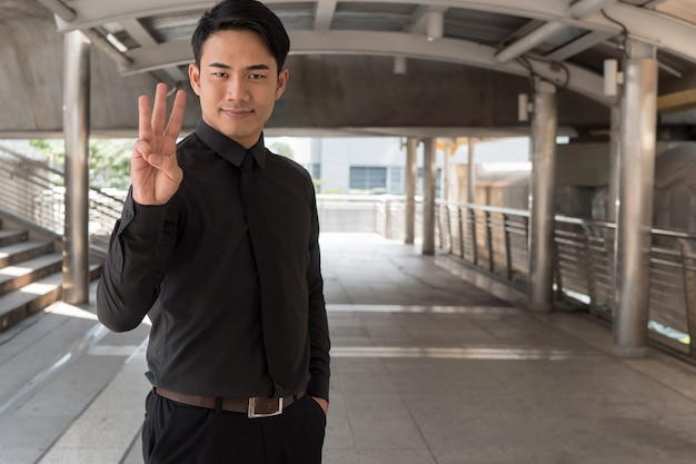 Homem de negócios apontando para o gesto de número 3 com a mão
