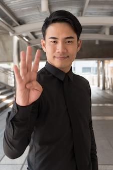 Homem de negócios apontando para o gesto de número 4 com a mão