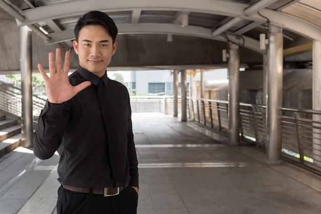 Homem de negócios apontando para o gesto de número 5 com a mão