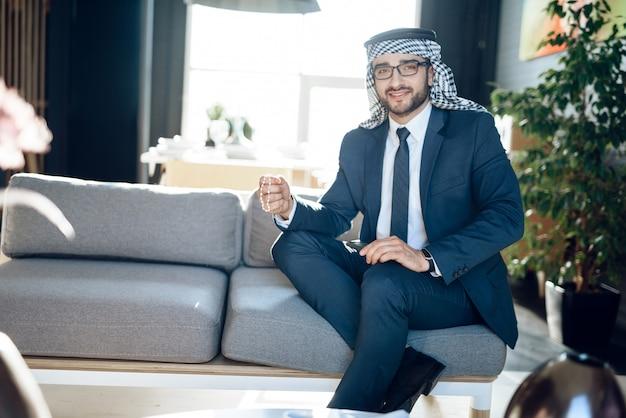 Homem de negócios árabe com os grânulos no sofá na sala de hotel.