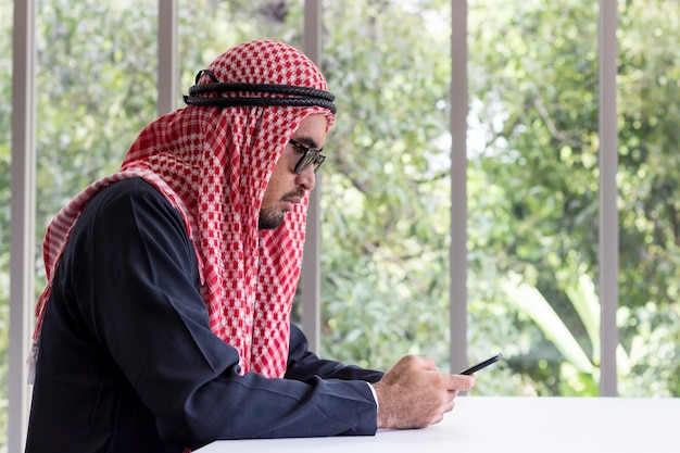 Homem de negócios árabe esperto que usa um smartphone para uma comunicação no escritório.