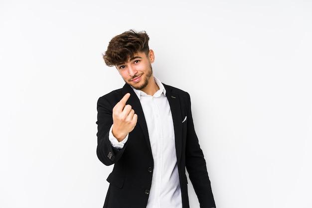 Homem de negócios árabe jovem isolado apontando com o dedo para você como se fosse um convite para se aproximar.